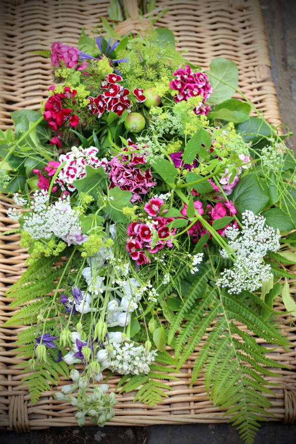 A seasonal May sheaf of natural funeral flowers with pink Sweet Williams, ferns, apples and aquilegia seedheads. For a natural burial so 100% biodegradable funeral flowers.