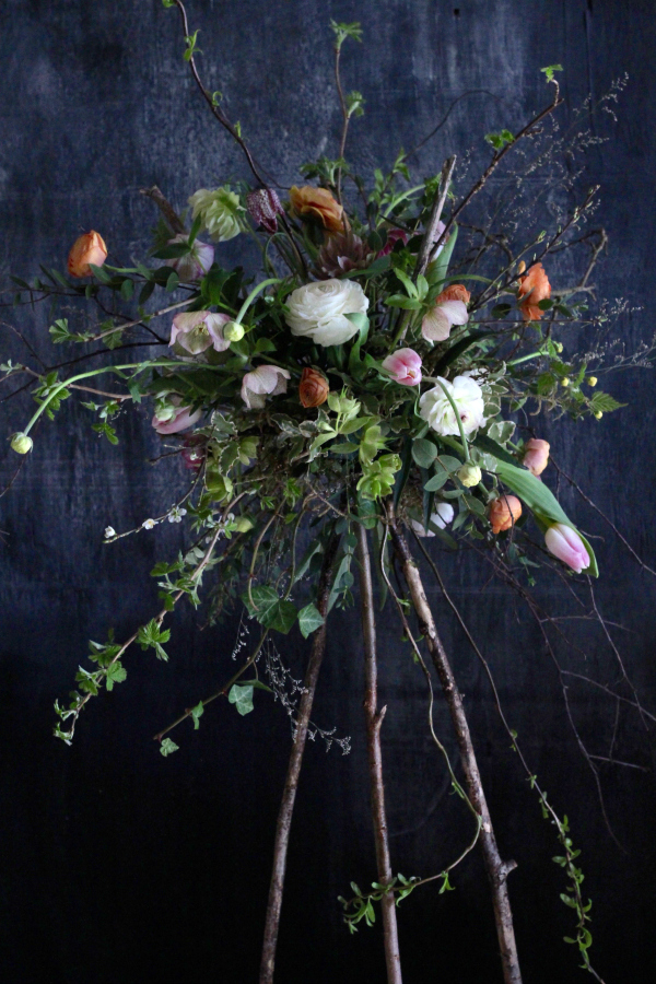 Seasonal spring flowers for rustic, natural venue flowers. A hazel tripod supports an escaping arrangement of pastel spring flowers. Tuckshop Flowers, Birmingham