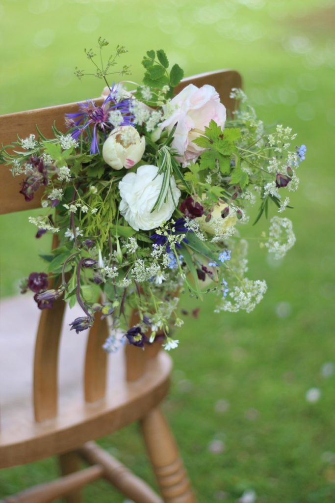A spring wedding chair back with freshly picked country flowers featuring white ranunculus, tulips and cow parsley for a natural wildflower effect. By Tuckshop Flowers, Birmingham. Available for weddings in the West Midlands, Worcestershire and Warwickshire