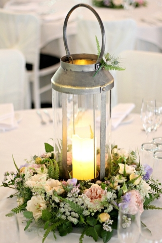 Wedding table centrepiece. A candlelit lantern set into a ring of wildflower style blooms. Pastel roses, ferns, frothy white ammi and sweetpeas give country garden charm as well as stunning perfume. Tuckshop Flowers, Birmingham
