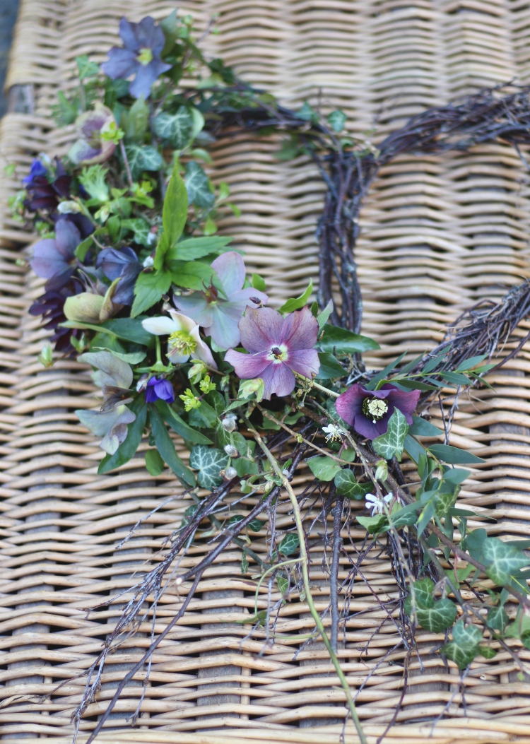 An understated heart-shaped wreath with dark hellebores and ivy. Informal, natural funeral flowers by Tuckshop Flowers, Florist, Birmingham