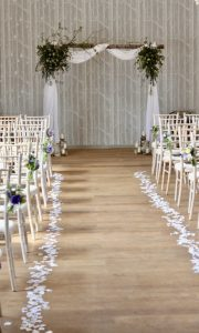 A silver birch arch dressed with simple cotton drapes and wild escaping foliage for a spring wedding at Hampton Manor, Warwickshire. Tuckshop Flowers, Birmingham.