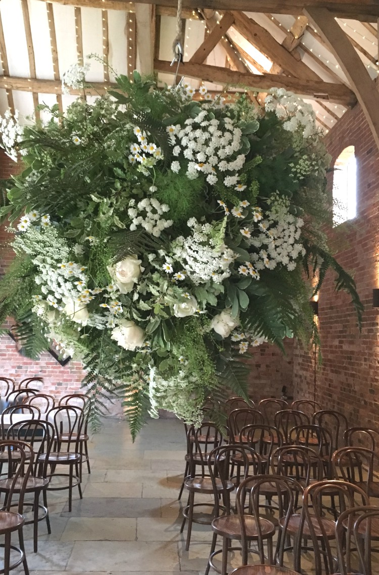 A hanging floral sphere for a summer wedding at Shustoke Barns. Full of greenery, wildflower style ingredients and premium scented garden roses by Tuckshop Flowers