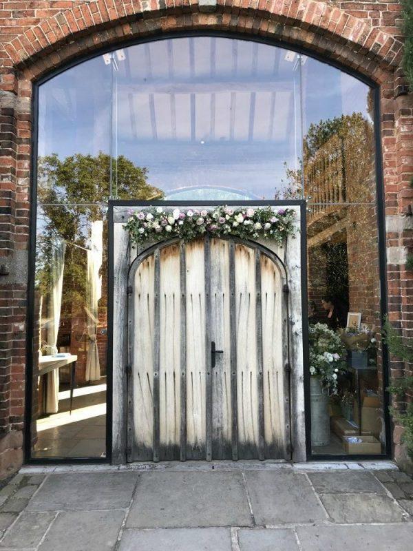 boho wedding flowers Shustoke Barns Warwickshire. Entrance door flowers by Tuckshop Flowers, Birmingham West Midlands.