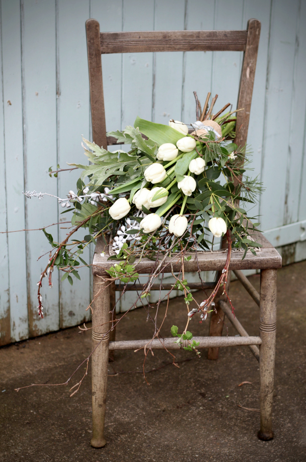 Early spring seasonal natural funeral flowers by Tuckshop Flowers Birmingham. Here a white seasonal sheaf with tulips and eucalyptus.