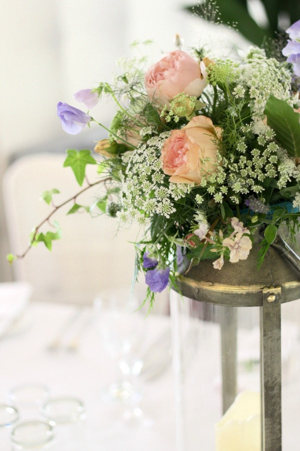 Table centrepiece flowers on a rustic lantern. Peach and blush roses with sweet peas, frothy ammi and natural greenery combine for an English Country Garden feel. Tuckshop Flowers, Birmingham.