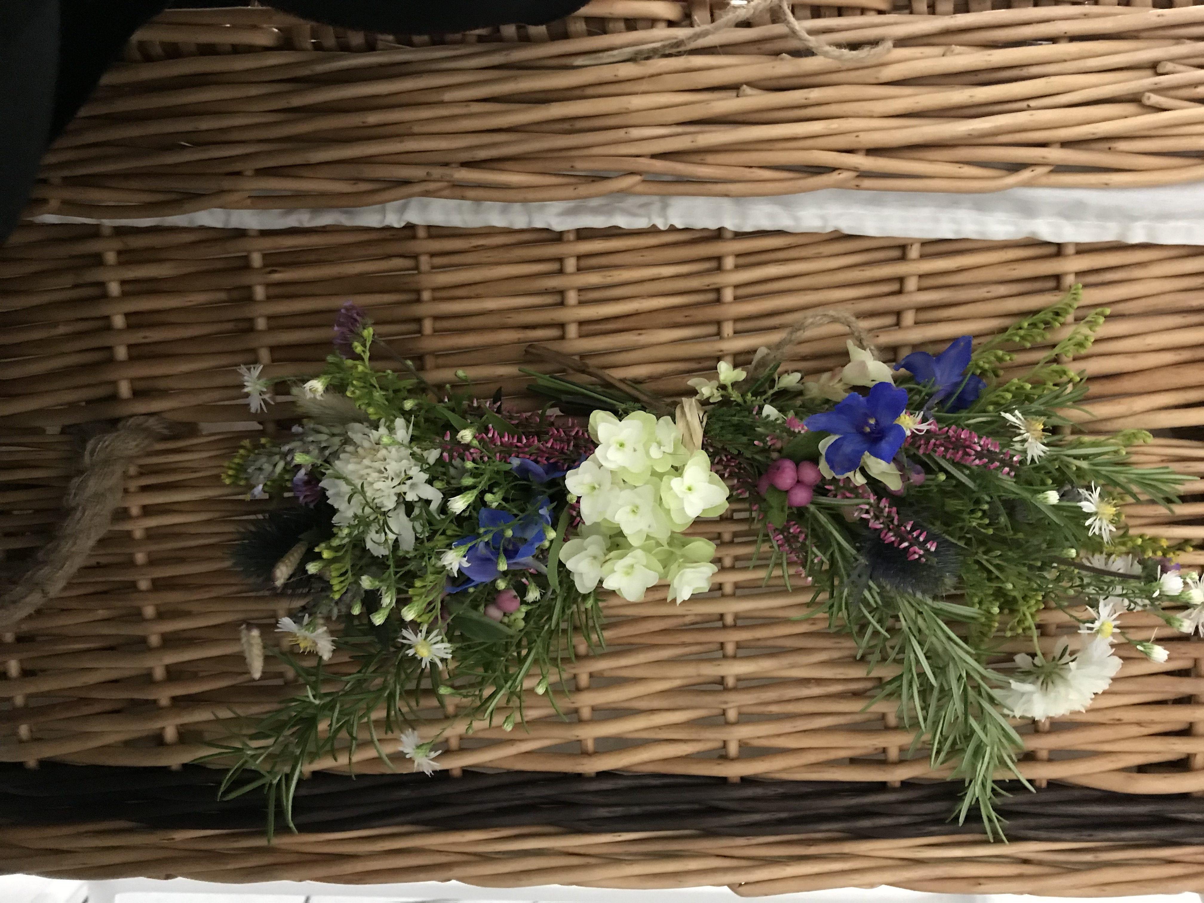 Natural wildflower style swags with heather and rosemary to decorate a willow coffin.